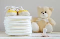 Några nappies på en vit trätabell Gymnastikskor, en fredsmäklare och en nallebjörn Royaltyfri Foto
