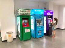 Några personer får pengarna från ATM-maskinen för att shoppa Royaltyfri Fotografi