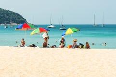 Några personer kopplar av på den vita sandstranden Royaltyfri Foto