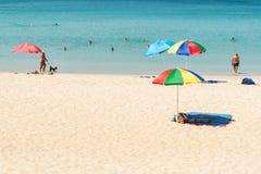 Några personer kopplar av på den vita sandstranden Royaltyfri Bild