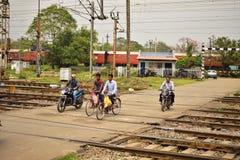 Några personer korsar en järnväg korsning i motorcykel eller på cirkulering nära den Tatanagar stångstationen royaltyfri fotografi