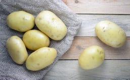 Några potatisar på en säck på en trätabell royaltyfri bild