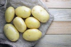 Några potatisar på en säck på en trätabell royaltyfria foton