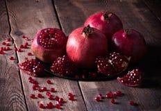 Några röda granatäpplen på den gamla trätabellen arkivbilder