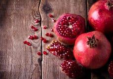 Några röda granatäpplen på den gamla trätabellen arkivbild