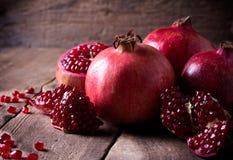 Några röda granatäpplen på den gamla trätabellen royaltyfri foto