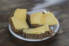 Några smörgåsar med chees på en gammal trätabell Arkivbilder