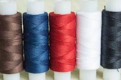 Några spolar av trådar på en textilbakgrund Royaltyfria Foton