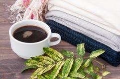 Några staplade varma stack tröjor som ligger på en träbakgrund Närliggande en kopp av varma kaffe och höstsidor Begreppet av waen Royaltyfri Fotografi
