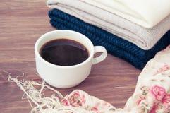 Några staplade varma stack tröjor som ligger på en träbakgrund Närliggande en kopp av varma kaffe och höstsidor Begreppet av waen Arkivbilder