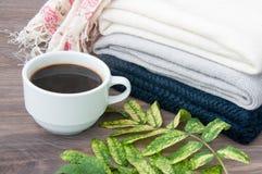 Några staplade varma stack tröjor som ligger på en träbakgrund Närliggande en kopp av varma kaffe och höstsidor Begreppet av waen Royaltyfri Bild
