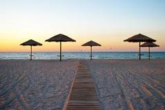 Några strandparaplyer ut ur sugröret på sandslingan nära solskenet för havsmorgonsommar tillbringar veckoslutet Arkivfoton