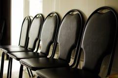 Några tomma stolar i mörkret Arkivfoto
