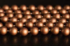 Några trådar av bruna pärlor på en svart bakgrund Arkivbilder