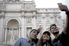 Några turister tar en bild i Trevi-springbrunn i Rome Royaltyfria Bilder
