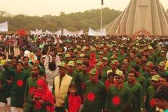 Når de har betalt respekt till den nationella minnesmärken i Bangladesh, går folket tillbaka Fotografering för Bildbyråer