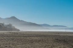 A névoa do oceano entra no por do sol na praia do canhão, Oregon, EUA imagens de stock royalty free