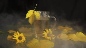A névoa está vindo em uma caneca de vidro transparente molhada da chuva de suportes quentes do chá no meio da paisagem do outono: filme