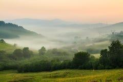 Névoa fria no nascer do sol quente nas montanhas Imagem de Stock