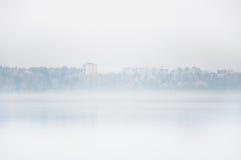 Névoa pesada no lago Senezh na queda de Solnechnogorsk no tempo calmo Vista dos prédios residenciais através do embaçamento imagem de stock