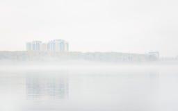 Névoa pesada no lago Senezh na queda de Solnechnogorsk no tempo calmo Vista dos prédios residenciais através do embaçamento imagem de stock royalty free