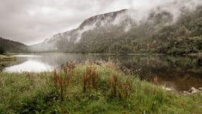 Névoa que pendura sobre o lago antes das montanhas Fotografia de Stock Royalty Free