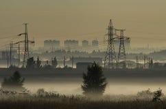 Névoa sobre campos e torres das linhas elétricas Foto de Stock Royalty Free