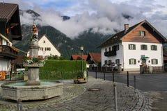 Névoa sobre o verão bávaro pequeno dos cumes de Alemanha do curso da rua de Oberau da vila das montanhas Imagem de Stock Royalty Free