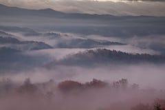 névoa Vermelho-hued da manhã sobre montanhas fumarentos Foto de Stock