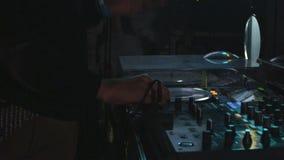 Níveis da volta das mãos do DJ do close up do movimento lento no console video estoque