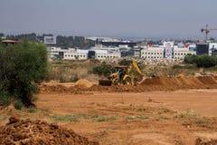 Nível alaranjado do trator a terra para a construção de um novo ho imagens de stock