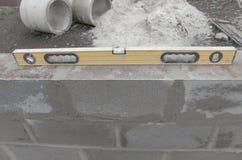 Nível amarelo bonito novo para construir no fundo dos cinderblocks Processo de construção Imagem de Stock Royalty Free