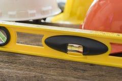 Nível amarelo da construção na tabela de madeira Fotos de Stock