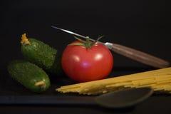 Nóż, czarna łyżka i sklep spożywczy ustawiający dwa zielonego ogórka, Fotografia Royalty Free