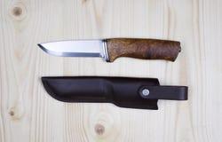 Nóż i sheath na płaskim sosnowym drewnie Obrazy Stock