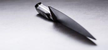 Nóż Kuchennego noża lying on the beach na nowożytnej betonowej tnącej desce fotografia stock