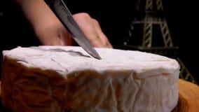 Nóż odcina kawałek Camembert i wyciąga zbiory
