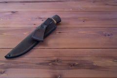 Nóż w scabbard na drewnianym stole Drewniany tło Obrazy Royalty Free