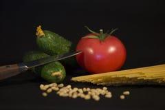 nóż z drewnianą rękojeścią, czarną łyżka, sklep spożywczy, jeden dojrzały pomidor, garść sezam i pas ustawiający dwa zielonego og Zdjęcia Royalty Free