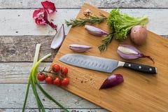 Nóż z zdrowym jedzeniem - warzywa, cebula, sałatka, pomidory, grula umieszczająca na tnącej desce z drewnianego tła odgórnym wido Zdjęcie Stock