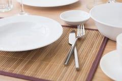Nóż, rozwidlenie i whiteware na stole Obrazy Stock