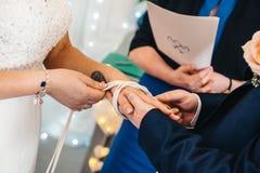 Nó tiding dos pares durante a cerimônia de casamento foto de stock