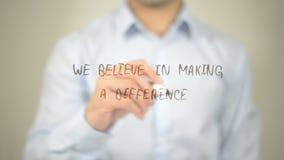 Nós acreditamos em fazer a diferença, escrita do homem na tela transparente imagens de stock royalty free