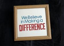 Nós acreditamos em fazer a diferença no quadro de madeira da foto fotos de stock