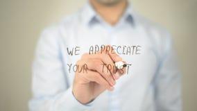 Nós apreciamos sua confiança, escrita do homem na tela transparente Foto de Stock Royalty Free