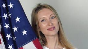 Nós bandeira estão nas mãos de uma mulher loura brilhante video estoque