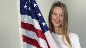 Nós bandeira estão nas mãos de uma mulher loura brilhante filme