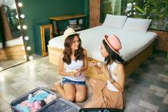 Nós estamos indo descansar duas amigas alegres bonitas em seu apartamento no sofá pusemos sua roupa em umas malas de viagem, meni fotografia de stock royalty free