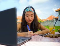 Nômada digital coreano asiático atrativo e feliz novo que trabalha fora relaxado com notas da escrita do laptop fotos de stock royalty free