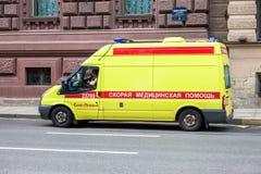 Nöd- ambulansbil med blått blinkande ljus på takmedeltalen Royaltyfri Fotografi